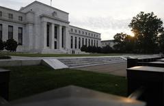 """Солнце встает к востоку от здания ФРС в Вашингтоне 31 июля 2013 года. Федеральная резервная система США сократила ежемесячную скупку активов на $10 миллиардов до $25 миллиардов и сохранила ключевую ставку в диапазоне 0,00-0,25 процента годовых, отметив на этот раз, что американская экономика """"несколько приблизилась"""" к долгосрочному ориентиру инфляции. REUTERS/Jonathan Ernst"""