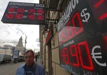 Мужчина у пункта обмена валют в Москве 20 февраля 2014 года. Рубль оставался в плюсе на полуденных торгах четверга после объявления накануне новых санкций ЕС, не затронувших пока крупных корпоративных и банковских имен. REUTERS/Maxim Shemetov