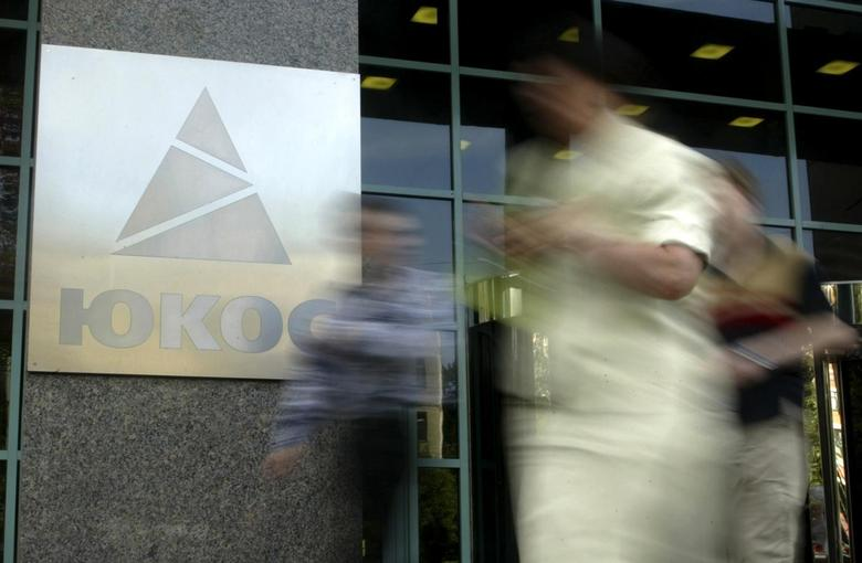 People walk by the Yukos oil company headquarters in Moscow in this July 8, 2004 file photo. REUTERS/Viktor Korotayev/Files