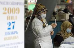 Торговка с сотовым телефоном на рынке в Ташкенте 24 декабря 2009 года. Российский оператор мобильной связи МТС сообщил в четверг, что урегулировал спор с Узбекистаном, арестовавшим его местные активы и отравившим за решетку топ-менеджеров, и рассчитывает вернуться на рынок 30-миллионной страны до конца года. REUTERS/Shamil Zhumatov