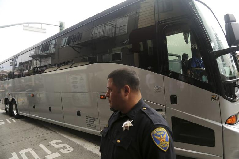 A San Francisco police officer stands in front of a Google commuter bus after clearing demonstrators blocking its path in the Mission District in San Francisco, California August 1, 2014. REUTERS/Robert Galbraith