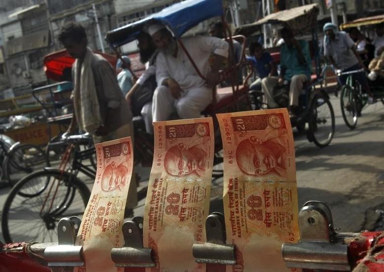 Cycle rickshaws move past a display of rupees at a roadside currency exchange stall in the old quarters of Delhi June 10, 2013. REUTERS/Anindito Mukherjee/Files
