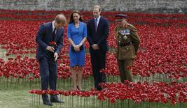 Britain's Prince Harry (L) plants a ceramic poppy watched Prince William (2nd R) and Catherine, Duchess of Cambridge at the Tower of London's 'Blood Swept Lands and Seas of Red' poppy installation to commemorate the 100th anniversary of the outbreak of World War One (WW1), in London August 5, 2014. REUTERS/Luke MacGregor