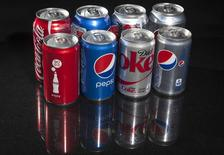 Regular and mini cans of Coke and Pepsi are pictured in this photo illustration in New York August 5, 2014. REUTERS/Carlo Allegri