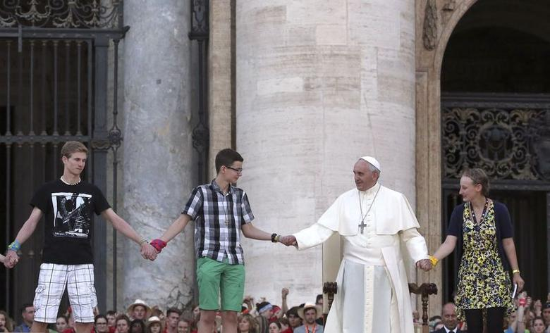 Pope Francis holds hands with youths during a meeting with altar workers in St Peter's square at the Vatican August 5, 2014.  REUTERS/ Stefano Rellandini