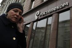 Женщина проходит мимо офиса Ростелекома в Москве 21 ноября 2012 года. Подконтрольный государству Ростелеком завершил создание СП с Tele2 Россия, создав национального оператора мобильной связи, обладающего лицензиями на связь третьего поколения (3G) и федеральной - на связь четвертого поколения LTE, говорится в сообщении Ростелекома в среду. REUTERS/Maxim Shemetov