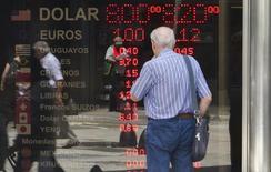 Un hombre observa los valores de diversas monedas en un panel en una casa de cambios en Buenos Aires, ene 31 2014. La incertidumbre sobre que tan rápido se acelerará la economía de Estados Unidos probablemente seguirá siendo el principal factor en los mercados de moneda de América Latina en los próximos meses, probablemente retrasando una esperada escalada del peso mexicano, según un sondeo de Reuters. REUTERS/Stringer (ARGENTINA - Tags: BUSINESS POLITICS)