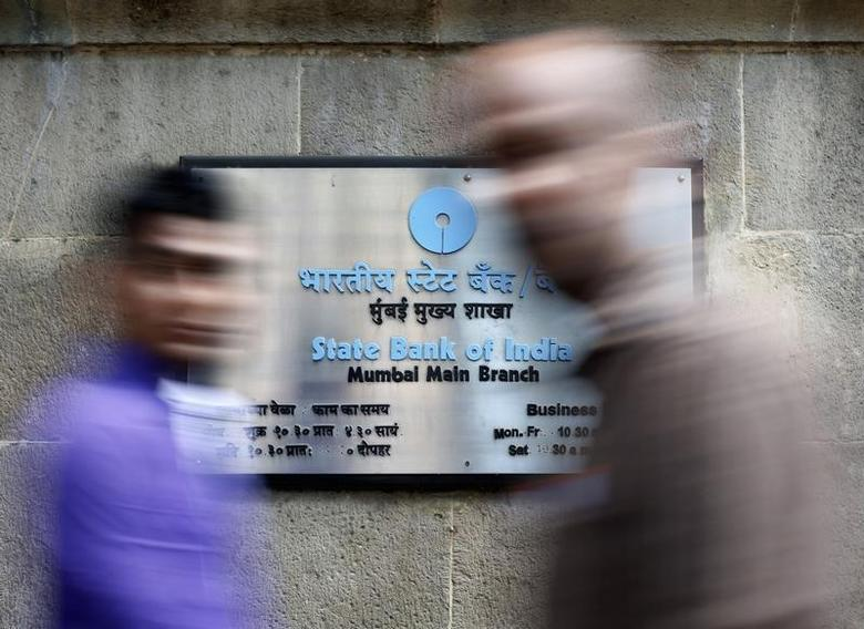 People walk in front of a signboard displayed at the head office of State Bank of India (SBI) in Mumbai February 14, 2014. REUTERS/Mansi Thapliyal/Files