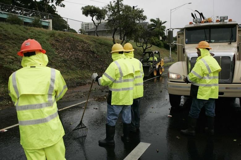 An emergency road crew clears off debris from a downed tree from the H1 freeway as Tropical Storm Iselle passes through the Hawaiian islands, in Honolulu, Hawaii, August 8, 2014.  REUTERS/Hugh Gentry
