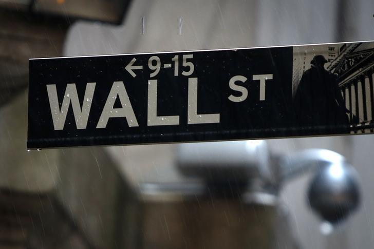 A Wall Street sign is pictured in the rain outside the New York Stock Exchange in New York June 9, 2014.     REUTERS/Carlo Allegri/Files