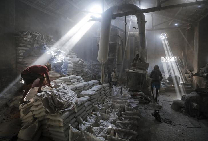 Employees work inside a limestone powder factory in an industrial area in Mumbai March 11, 2014. REUTERS/Danish Siddiqui/Files