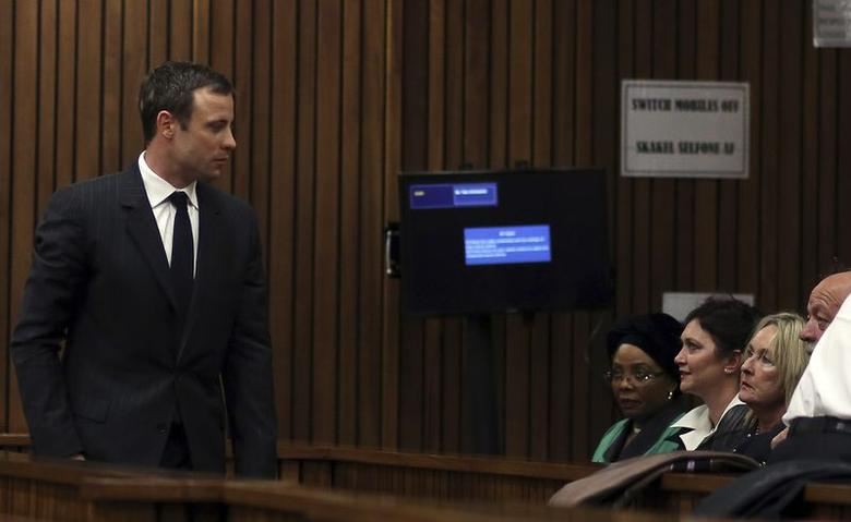 June Steenkamp (seated 3rd L), with her husband Barry (seated 4th L), parents of Reeva Steenkamp, look on as South African Olympic and Paralympic sprinter Oscar Pistorius (L) enters a court in Pretoria August 8, 2014.  REUTERS/Themba Hadebe/Pool