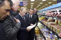 Президент России Владимир Путин (в центре) в магазине в Москве 24 июня 2009 года. Масштаб издержек от конфликта на Украине для экономики РФ существенно вырос в последнее время: цена решений как западных, так и российских властей в краткосрочной перспективе будет включать увеличение чистого оттока капитала, ускорение снижения курса рубля, всплеск инфляции и отсутствие возможности возобновления сколько-нибудь заметного экономического роста, считают эксперты Высшей школы экономики. REUTERS/Alexei Nikolsky/RIA Novosti/Pool