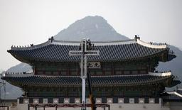 Labourers install a giant cross in front of Gwanghwamun, main gate of the royal Gyeongbok Palace, ahead of Pope Francis' visit in central Seoul August 12, 2014.   REUTERS/Kim Hong-Ji