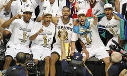 (L-R) San Antonio Spurs' Kawhi Leonard, Tony Parker of France, Tim Duncan, Manu Ginobili of Argentina, and Patty Mills pose with the Larry O'Brien trophy after the Spurs defeated the Miami Heat in Game 5 of their NBA Finals basketball series in San Antonio, Texas, June 15, 2014. REUTERS/Mike Stone