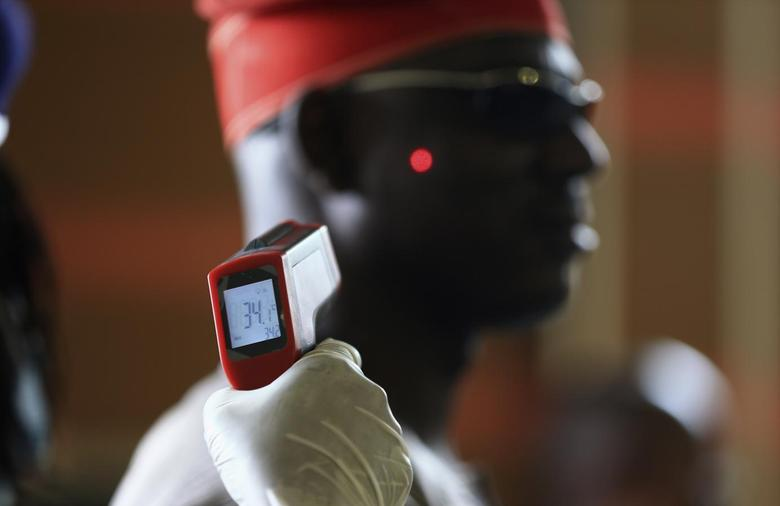 A man has his temperature taken using an infrared digital laser thermometer at the Nnamdi Azikiwe International Airport in Abuja, August 11, 2014.   REUTERS/Afolabi Sotunde