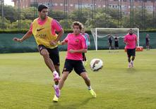 Barcelona's new player Luis Suarez (L) kicks the ball, next to Sergi Roberto (C) during a training session at Ciutat esportiva Joan Gamper in Sant Joan Despi near Barcelona August 15, 2014.   REUTERS/Gustau Nacarino