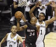 Miami Heat's Ray Allen (C) looks to pass under pressure from San Antonio Spurs' Tim Duncan (R) and Tony Parker of France during the second half in Game 5 of their NBA Finals basketball series in San Antonio, Texas, June 15, 2014. REUTERS/Mike Stone