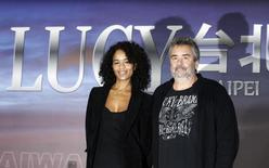 """French film director Luc Besson (R) and his wife and producer Virginie Silla pose for photographs during a news conference for his movie """"Lucy"""" in Taipei November 1, 2013.  REUTERS/Pichi Chuang"""