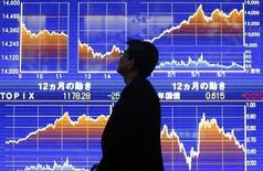 Мужчина у брокерской конторы в Токио 25 октября 2013 года. Азиатские фондовые рынки выросли во вторник благодаря экономической статистике США и геополитическим новостям. REUTERS/Yuya Shino