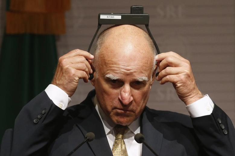 California Governor Jerry Brown adjusts his earpiece during a news conference at Memoria y Tolerancia museum in Mexico City July 28, 2014. REUTERS/Edgard Garrido