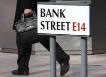 A worker passes a sign for Bank Street in the Canary Wharf financial district in London October 21, 2010. REUTERS/Luke MacGregor