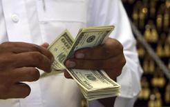 Ювелир пересчитывает долларовые купюры в магазине в Мекке 20 октября 2012 года. Доллар США торгуется вблизи 11-месячного максимума к корзине основных валют после публикации протокола июльского совещания ФРС. REUTERS/Amr Abdallah Dalsh