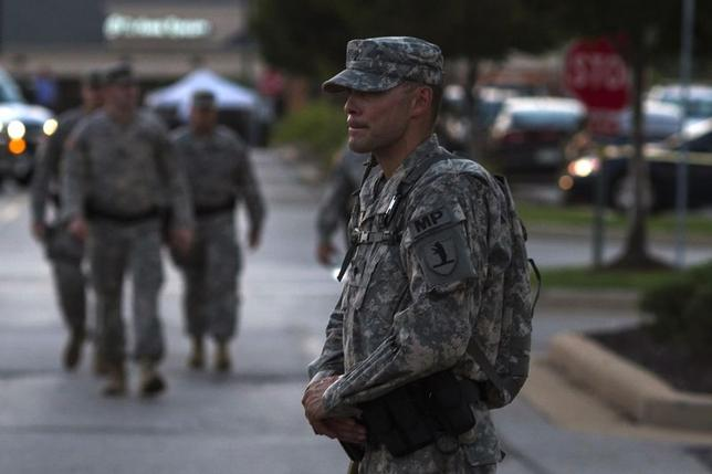 A member of the National Guard stands guard at a staging area inside a shopping center parking lot in Ferguson, Missouri August 21, 2014. REUTERS/Adrees Latif