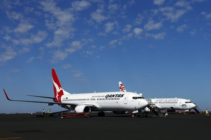 A Qantas Airlines Boeing 737 plane sits next to a Virgin Australia Boeing 737 plane at the Port Hedland airport in the Pilbara region of western Australia December 3, 2013.   REUTERS/David Gray
