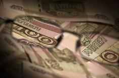 Рублевые купюры в Москве 17 февраля 2014 года. Чистая прибыль российского ритейлера Дикси во втором квартале 2014 года увеличилась в 4 раза до 1,3 миллиарда рублей благодаря снижению налоговой ставки из-за реорганизации, сообщила компания в пятницу. REUTERS/Maxim Shemetov