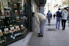 Una persona observa los precios de bebestibles en una tienda en el centro de Santiago, ago 26 2014. La economía chilena habría crecido un 0,2 por ciento interanual en julio, su desempeño mensual más débil en más de cuatro años, tras la contracción que anotaron la manufactura y la minería y el moderado avance del consumo, mostró el viernes un sondeo de Reuters. REUTERS/Ivan Alvarado