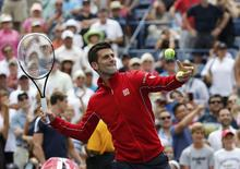 Novak Djokovic of Serbia hits balls into the crowd after defeating Sam Querrey of the U.S. at the 2014 U.S. Open tennis tournament in New York, August 30, 2014.   REUTERS/Ray Stubblebine (UNITED STATES  - Tags: SPORT TENNIS)