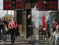Прохожие у пункта обмена валют в Москве 2 сентября 2014 года. Рубль продолжил снижение во вторник из-за угрозы введения Западом новых санкций против России, но достигнутые накануне экстремумы устояли на фоне перепроданности российской валюты и появления на рынке экспортных продаж валюты. REUTERS/Sergei Karpukhin