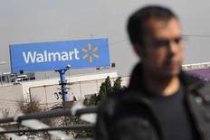 Una persona camina cerca de un letro de Wall-Mart en Ciudad de México. Fotografía de archivo, 11 junio, 2013. Wal-Mart de México (Walmex), la cadena minorista más grande del país, dijo el miércoles que sus ventas comparables subieron un 3.5 por ciento interanual en agosto, beneficiadas por un calendario favorable, y anunció un recorte en su plan de inversiones para este año. REUTERS/Edgard Garrido