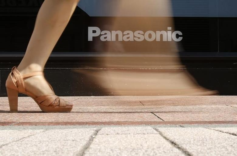 A woman walks past a logo of Panasonic Corp outside an electronics retail store in Tokyo July 31, 2014. REUTERS/Yuya Shino