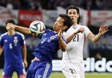 Edison Cavani, do Uruguai, briga pela bola com o japonês Yuto Nagatomo durante amistoso em Sapporo. 05/09/2014 REUTERS/Kyodo
