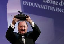 """Swedish director Roy Andersson holds the Golden Lion prize for his movie """"A Pigeon Sat on a Branch Reflecting on Existence"""" during the award ceremony at the 71st Venice Film Festival September 6, 2014. REUTERS/Tony Gentile"""