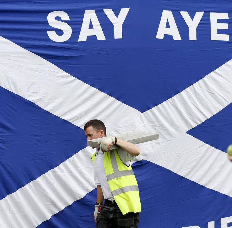 A workman walks past a Scottish saltire in Kilmarnock, Scotland September 3, 2014. REUTERS/Russell Cheyne