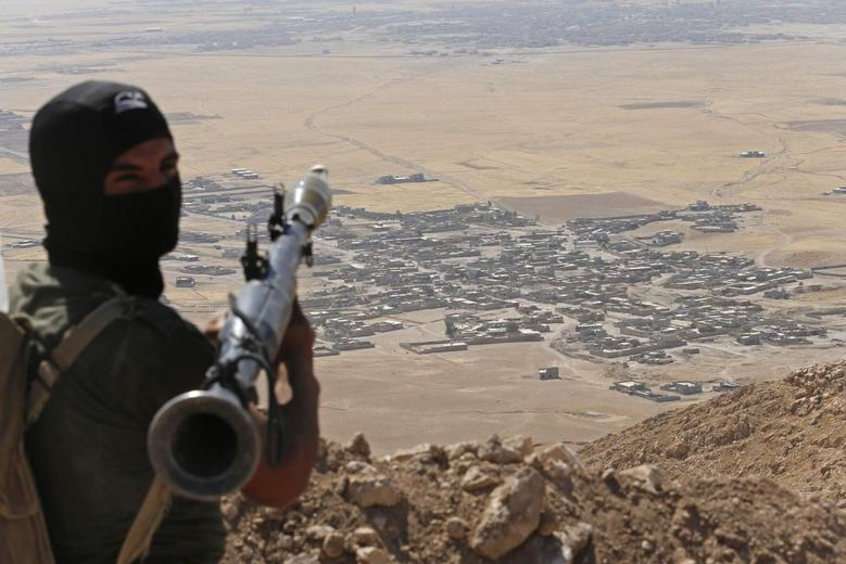 A Kurdish Peshmerga fighter holds a a rocket-propelled grenade launcher as he takes up position in an area overlooking Baretle village (background), which is controlled by the Islamic State, in Khazir, on the edge of Mosul September 8, 2014.  REUTERS/Ahmed Jadallah
