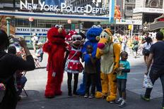 People dressed in costumes pose for a photograph with a family in the Times Square region of New York August 11, 2014.  REUTERS/Lucas Jackson