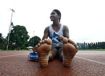 Heptathlete Swapna Barman prepares to wear her track shoes before a practice session at Salt Lake stadium in Kolkata August 29, 2014. REUTERS/Rupak De Chowdhuri