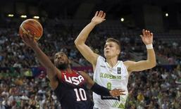 Kyrie Irving of the U.S. (L) goes up for a basket past Slovenia's Edo Muric during their Basketball World Cup quarter-final game in Barcelona September 9, 2014.       REUTERS/Albert Gea