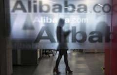 An employee is seen behind a glass wall with the logo of Alibaba at the company's headquarters on the outskirts of Hangzhou, Zhejiang province, April 23, 2014.REUTERS/Chance Chan
