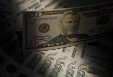 Купюры российского рубля и доллара США в Москве 17 февраля 2014 года. Рубль начал торги пятницы падением котировок до новых исторических минимумов после принятия санкций ЕС против России и перед объявлением новых американских ограничений, из-за спроса на валюту США, как внешнего так и внутреннего, а также на фоне низких нефтяных цен. REUTERS/Maxim Shemetov