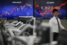 Una persona pasa frente una pantalla electrónica que muestra el índice KOSPI en el banco de Seoul, 07 febrero, 2014.Datos reportados el sábado mostraron que la producción de las fábricas chinas creció en agosto a su ritmo más débil en casi seis años, mientras que la exnapsión en otros sectores clave también se ha enfríado. REUTERS/Kim Hong-Ji