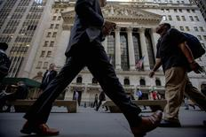 Morning commuters pass by the New York Stock Exchange September 15, 2014. REUTERS/Brendan McDermid