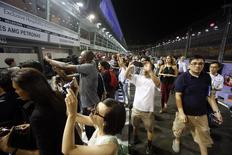 Fans take photos in the pit during a pit walk ahead of the Singapore F1 Grand Prix night race September 18, 2014. REUTERS/Edgar Su