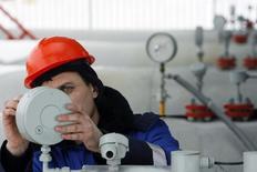 Работник Газпрома на газокомпрессорной станции в Судже 14 января 2009 года. Агрессивная политика конкурентов, стагнирующая экономика России и прекращение поставок газа на Украину может обернуться в 2014 году историческим минимумом добычи Газпрома, на доходы которого очень расcчитывает балансирующее на грани рецессии правительство. REUTERS/Denis Sinyakov