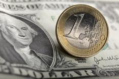 Однодолларовая купюра и монета в 1 евро в Варшаве 18 января 2011 года. Курс доллара близок к двухлетнему максимуму к корзине основных валют за счет ожиданий раннего повышения процентных ставок ФРС. REUTERS/Kacper Pempel