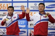 North Korea's Om Yun Chol (L) and Kim Un Guk (R) pose with their gold medals during a news conference at the 17th Asian Games in Incheon September 23, 2014. REUTERS/Rob Dawson